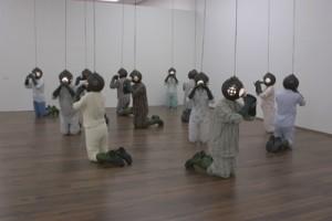 Kicsiny Balázs: Ivócsarnok, 2005, 12 db poliészter testöntvény, női-férfi pizsama, gumicsizma, gumikesztyű, festett lámpabura, ezüstözött kehely, elektromos vezeték, elektromos ég